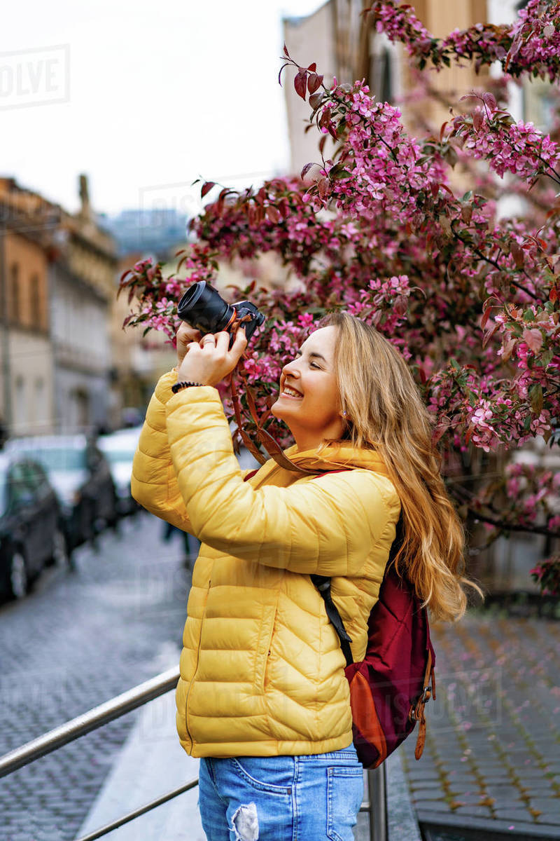 Young tourist woman taking pictures with a camera in old town Europe Royalty-free stock photo