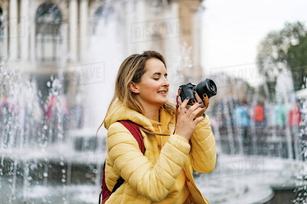 Young tourist woman with a camera taking picture in old town Europe. Royalty-free stock photo