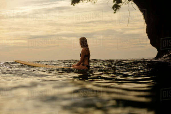 Woman surfing in sea against cloudy sky during sunset Royalty-free stock photo