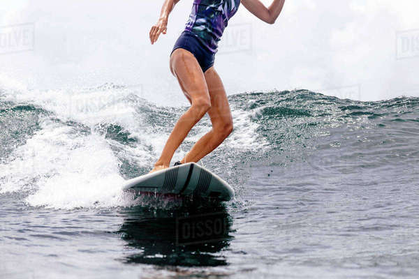 Low section of woman surfboarding in sea Royalty-free stock photo
