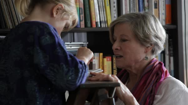 Handheld shot of grandmother looking at granddaughter reading book Royalty-free stock video