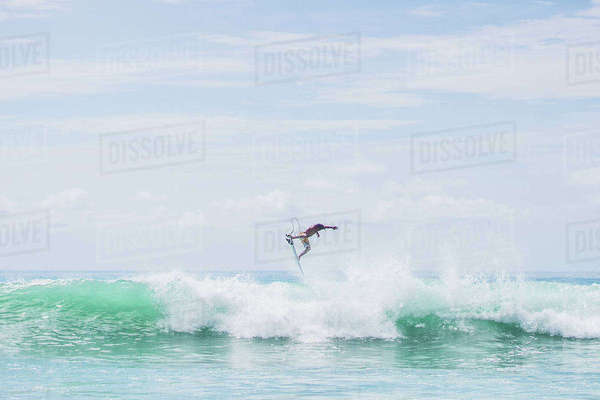 Determined male surfer jumping on huge sea waves against sky Royalty-free stock photo