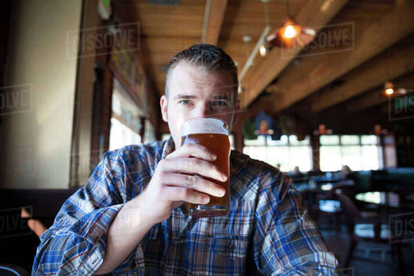 Portrait of man having beer while sitting in restaurant Royalty-free stock photo