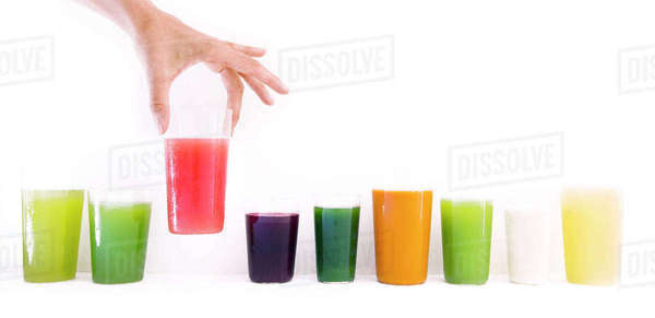 Cropped image of woman holding fresh juice glass against white wall Royalty-free stock photo