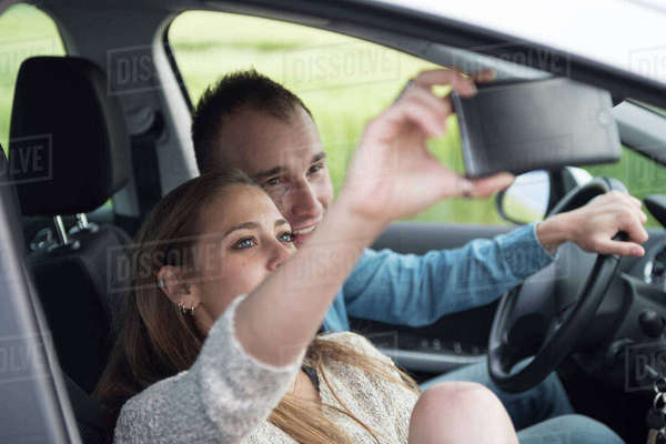 Woman taking selfie with man through smart phone in car during vacation Royalty-free stock photo