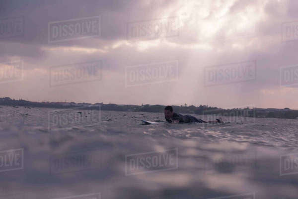 Man surfing in sea at dusk Royalty-free stock photo