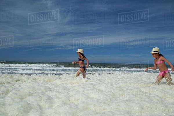 Sisters playing in sea foam at beach against sky Royalty-free stock photo