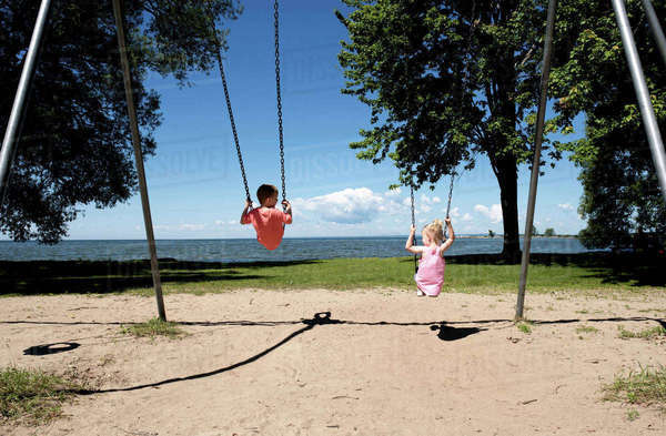 Rear view of brother and sister swinging at playground against sea Royalty-free stock photo