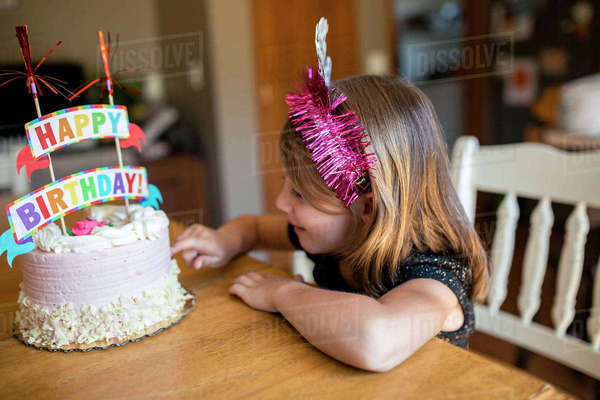 High angle view of girl touching birthday cake while sitting on chair at home Royalty-free stock photo