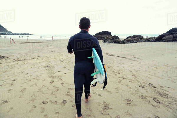 Rear view of man in wetsuit carrying surfboard while walking on beach Royalty-free stock photo