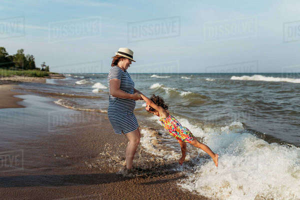 Playful mother spinning daughter at beach against sky Royalty-free stock photo