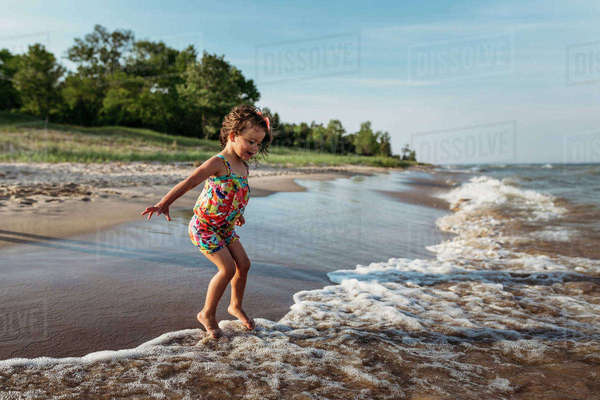 Playful girl jumping in waves at beach against sky Royalty-free stock photo