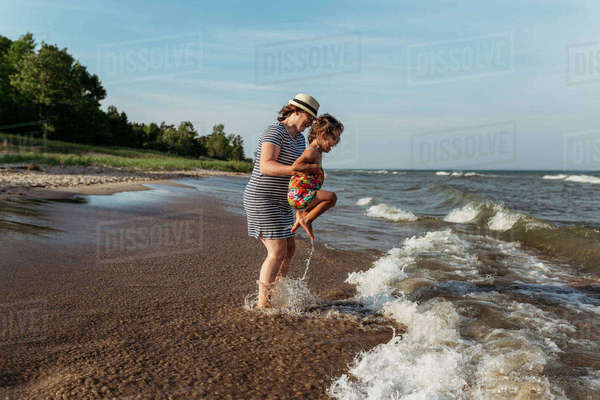 Mother and daughter playing in waves at beach against sky Royalty-free stock photo
