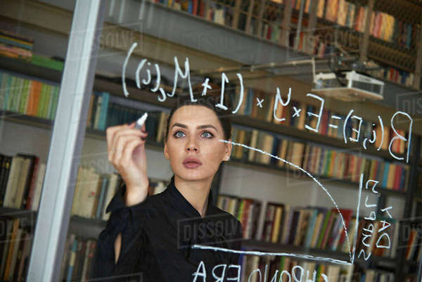 Serious businesswoman writing formula on glass wall at office Royalty-free stock photo
