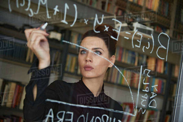 Businesswoman writing formula on glass wall Royalty-free stock photo