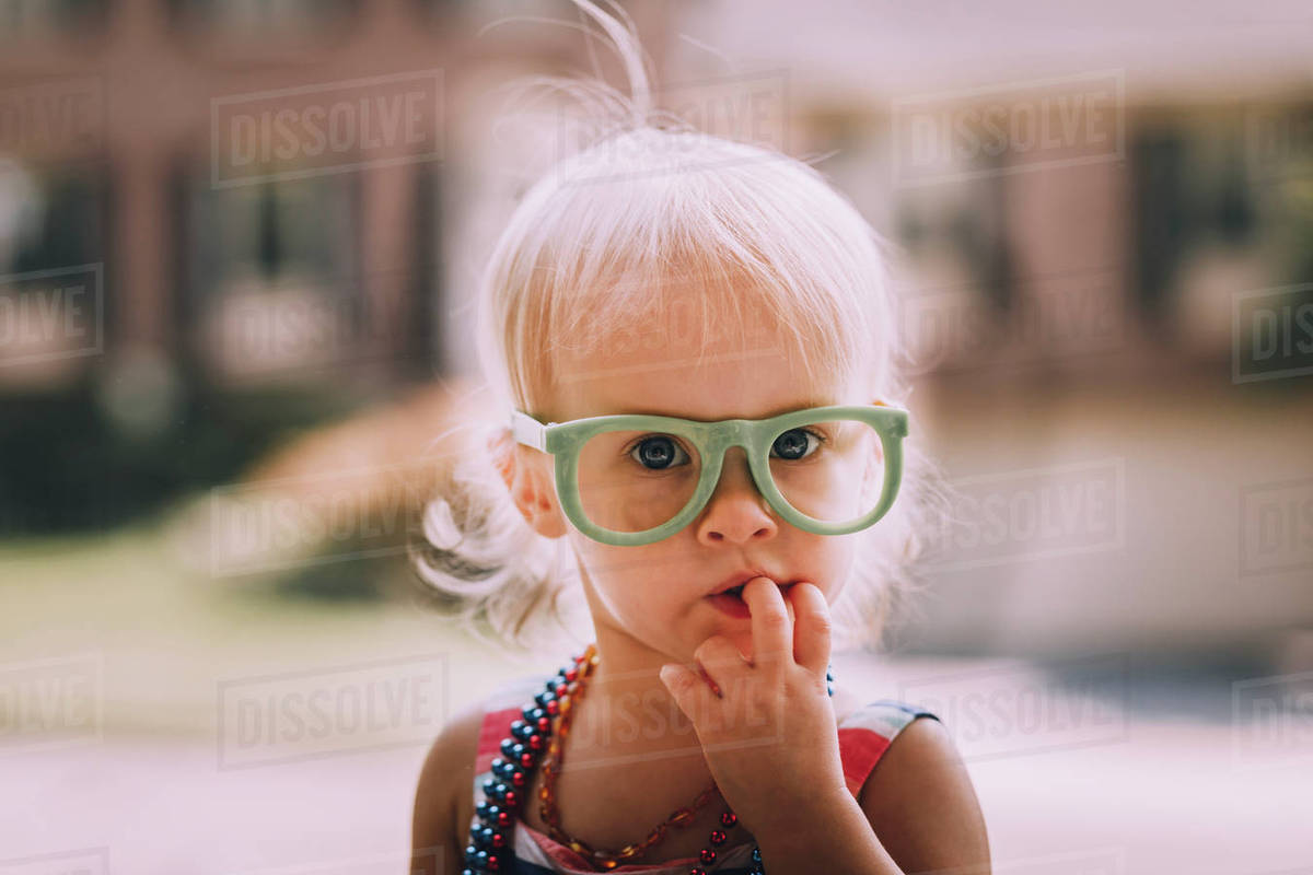 f6bbde3b08 Portrait of cute baby girl wearing eyeglasses with finger in mouth ...