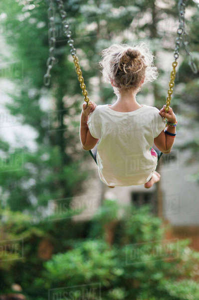 Rear view of carefree girl swinging at park Royalty-free stock photo
