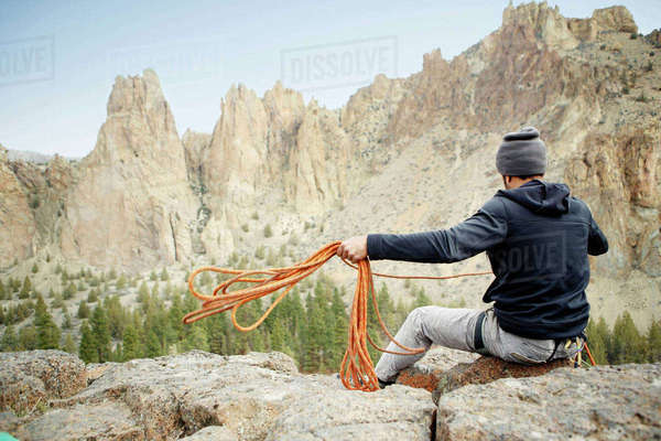 Rear view of rock climber throwing rope while siting on mountain Royalty-free stock photo