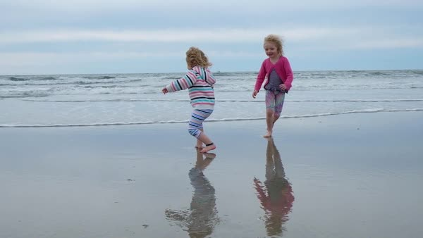 Handheld shot of happy sisters running from waves on sea shore at Diamond Beach Royalty-free stock video