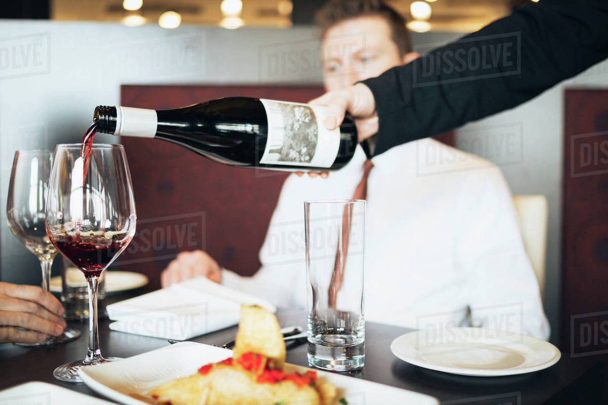 Cropped hand of waiter pouring wine in glass for business ...
