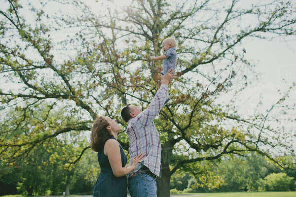 Happy father throwing baby boy in air Royalty-free stock photo