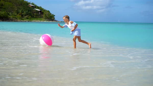 Cute little girl playing with ball on beach, kids summer sport outdoors - Stock Video Footage - Dissolve