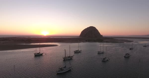 Aerial flyover of Morro Bay at sunset with boats in foreground and Morro Rock in background. Royalty-free stock video
