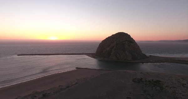 Aerial flyover of Morro Bay at sunset with Morro Rock in background. Royalty-free stock video