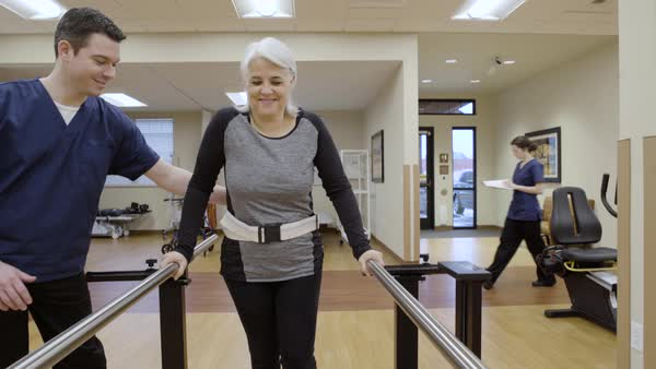 Medium shot of a senior woman walking in parallel bars Royalty-free stock video