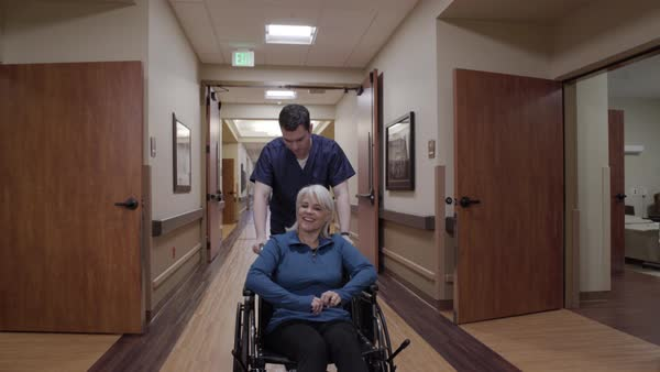 Steadicam shot of a male nurse pushing a senior woman in a wheelchair Royalty-free stock video