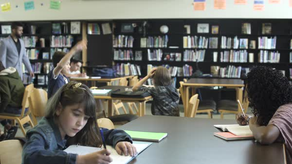 Wide shot of teacher in high school library helping pupil Royalty-free stock video