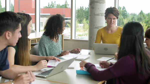 Female teacher talking to students while sitting together at a table Royalty-free stock video