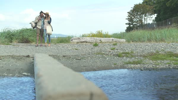 A couple crossing a stream on a pier Royalty-free stock video
