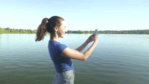 A young woman taking a photograph on a pier Royalty-free stock video