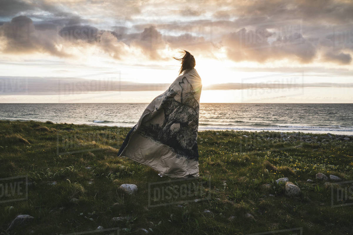 Rear view of a woman wrapped in blanket standing on beach during sunset Royalty-free stock photo