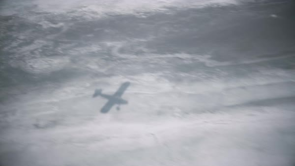 Aerial shot of an airplane shadow on a frozen river in Alaskan Royalty-free stock video