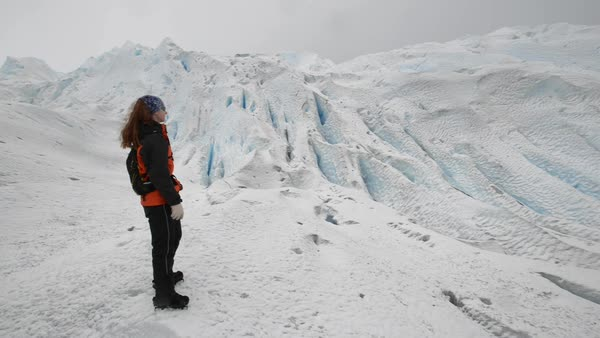 Panning shot of a woman standing on a glacier Royalty-free stock video
