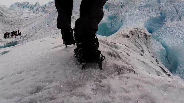 Close-up shot of a person walking on an icy mountain in a climbing boots Royalty-free stock video