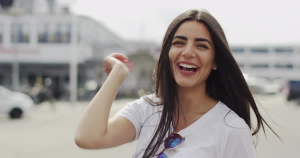 Fun vivacious pretty woman with long brown hair pulling faces and gesturing behind her head with her fingers, close up head and shoulders in an urban street Royalty-free stock video