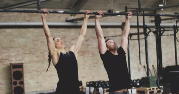 Fit man and woman exercising in gym, doing pull ups and laughing Royalty-free stock video