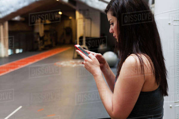 Sweden, Young woman texting at gym Royalty-free stock photo