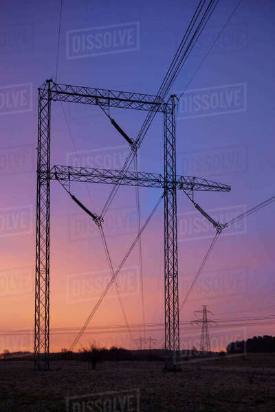 Sweden, Skane, Barseback, Electricity pylons against dramatic sky at sunset Royalty-free stock photo
