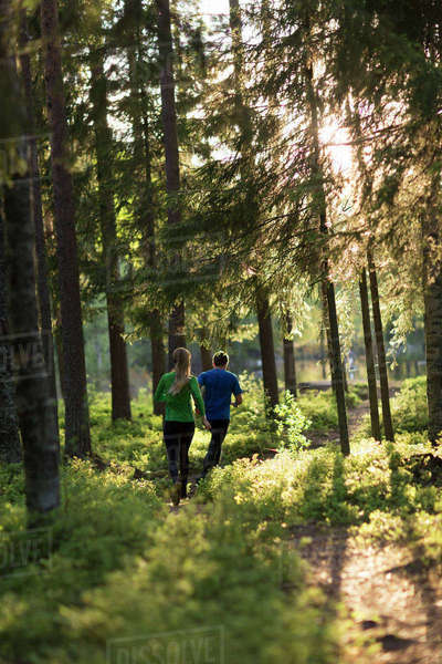 Sweden, Vasterbotten, Grossjons Nature Reserve, Man and woman running in forest Royalty-free stock photo