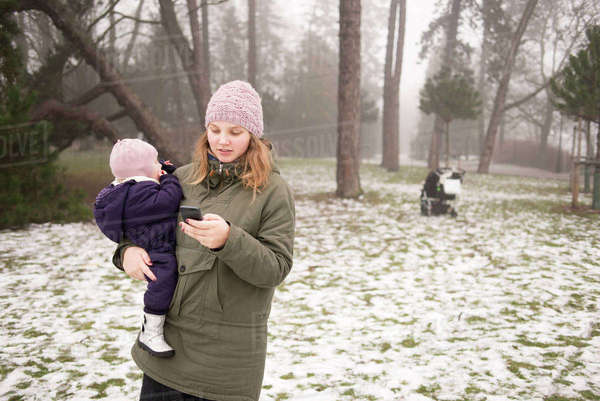 Sweden, Skane, Malmo, Young woman holding daughter (12-17 months) and using phone Royalty-free stock photo