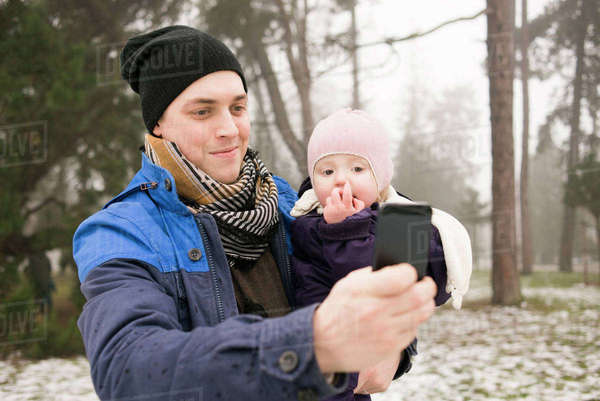 Sweden, Skane, Malmo, Young man taking selfie with daughter (12-17 months) in park Royalty-free stock photo