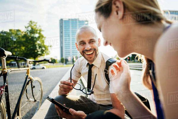 Germany, Berlin, Man and woman sitting on sidewalk Royalty-free stock photo