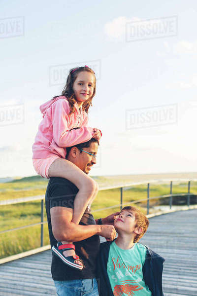 Germany, Schleswig-Holstein, Kreis Nordfriesland, Sankt Peter-Ording, Portrait of father with daughter (10-11) and son (8-9) Royalty-free stock photo