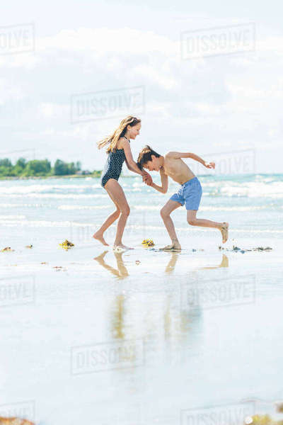 Sweden, Oland, Kopingsvik, Girl (10-11) and boy (8-9) dancing on beach Royalty-free stock photo