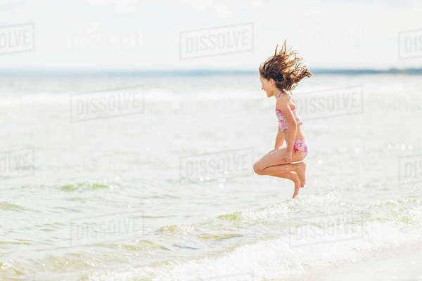 Sweden, Skane, Ahus, Aspet, Girl (8-9) jumping into sea Royalty-free stock photo