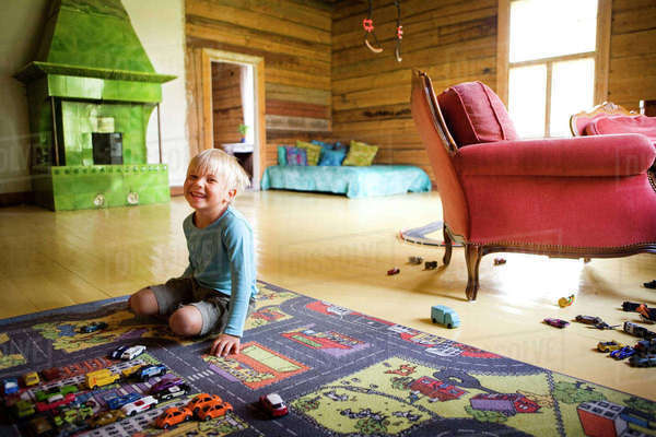 Finland, Boy (4-5) kneeling on multi colored carpet in room Royalty-free stock photo
